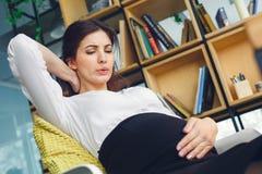 Ciężarna biznesowa kobieta pracuje przy biurowego macierzyństwa brzucha siedzącym bólem zdjęcia stock