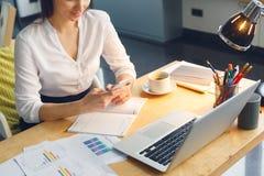Ciężarna biznesowa kobieta pracuje przy biurowego macierzyństwa siedzącym gawędzeniem używać smartphone fotografia royalty free