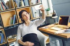 Ciężarna biznesowa kobieta pracuje przy biurowym macierzyństwa obsiadaniem bierze selfie fotografie zdjęcia royalty free