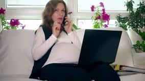Ciężarna biznesowej kobiety kobieta opowiada telefon i działanie z komputerem w domu zbiory