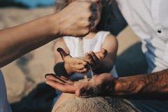 Ciężarna caucasian matka nalewa piasek w ręki jej córka Ręki matka i dziecko Bawić się z fotografia royalty free