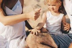 Ciężarna caucasian matka nalewa piasek w ręki jej córka Ręki matka i dziecko Bawić się z zdjęcie stock