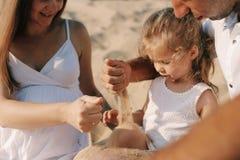 Ciężarna caucasian matka nalewa piasek w ręki jej córka Ręki matka i dziecko Bawić się z zdjęcia stock