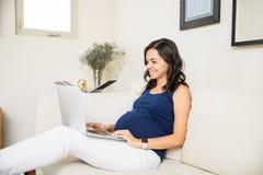 Ciężarna dama Używa laptop Podczas Jej wolnego czasu Zdjęcia Royalty Free