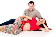 Ciężarna dziewczyna, kłamstwa z czerwonym faborkiem na jego żołądku, mąż Zdjęcia Royalty Free