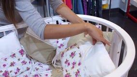 Ciężarna dziewczyna wybiera dziecka łóżko polowe w dziecka ` s sklepie odzieżowym, zakończenie zbiory