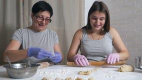Ciężarna dziewczynka i jej matka siedzą przy stole w kuchni domowej i przygotowują kluski z mielonym mięsem na lunch, toczą się zbiory