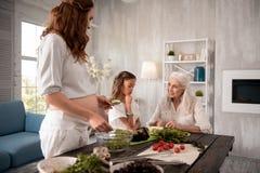 Ciężarna gospodyni domowa gotuje zdrowej sałatki dla jej córki i matki Fotografia Royalty Free