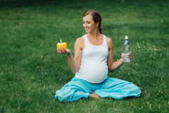 Ciężarna joga kobieta z butelką wodny i dzwonkowy pieprz w lotosowej pozyci, park, trawa plenerowy, las Zdjęcie Stock