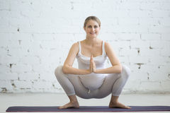 Ciężarna młoda kobieta robi prenatal joga Girlanda, Malasana poza obrazy stock