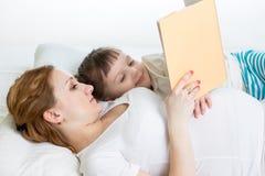 Ciężarna matka czyta książce jej dzieciak dziewczyny zdjęcie stock