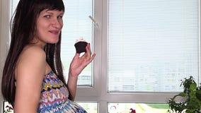 Ciężarne żeńskie ręki pieścą brzucha i szczęśliwego kobiety łasowania tort z apetytem zbiory