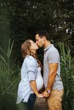 Ciężarne pary mienia ręki i całowanie each inny obrazy royalty free