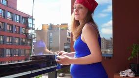 Ciężarnej domowej żony kobiety czysty szkło i spojrzenie przez okno w domowym balkonie zbiory wideo