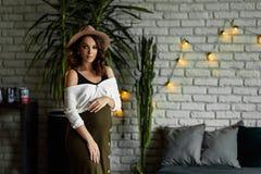 Ciężarni europejscy kobieta stojaki w sypialni w białej bluzce i zieleni omijają z beżowym kapeluszem w ciemnym mieszkaniu, elega obraz royalty free