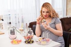 Ciężarni młodej kobiety łasowania cukierki Fotografia Stock