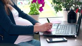 Ciężarny biznesowej kobiety brzuch używać laptop i robić notatce zdjęcie wideo