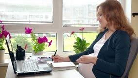 Ciężarny biznesowej kobiety pisać na maszynie laptop i robić notatki w notatniku zdjęcie wideo