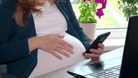 Ciężarny biznesowej kobiety use smartphone i uderzenie pieścimy brzucha przy jej miejscem pracy zdjęcie wideo