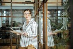 Ciężarny bizneswoman jest ubranym szkła i słuchawki w biurze zdjęcia stock