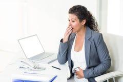 Ciężarny bizneswoman patrzeje oddalony podczas gdy ziewający Fotografia Stock
