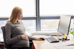 Ciężarny bizneswoman z komputerem przy biurem Obrazy Royalty Free