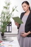 Ciężarny bizneswoman z książką. obraz royalty free