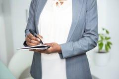 Ciężarny bizneswomanu writing na notatniku zdjęcie royalty free