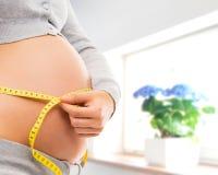 Ciężarny brzuch młoda kobieta w pięknym wnętrzu zdjęcia stock