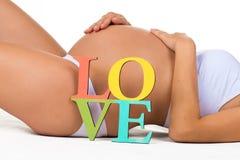 Ciężarny brzuch z szyldową miłością Pojęcie brzemienności i miłości kobieta w ciąży dziecko Fotografia Stock