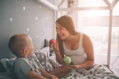 Ciężarny matki i chłopiec syn je brzoskwini w łóżka t domu w ranku i jabłka Przypadkowy styl życia wewnątrz obraz royalty free