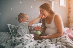 Ciężarny matki i chłopiec syn je brzoskwini w łóżka t domu w ranku i jabłka Przypadkowy styl życia wewnątrz obrazy royalty free