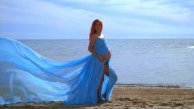 Ciężarny model w błękit sukni lataniu na wiatrze Romantyczna fotografii sesja zbiory