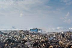 Ciężarowa jazda przy śmieciarskim usypem pełno dym, ściółka, klingeryt butelki, banialuki i grat przy tropikalną wyspą, obraz royalty free