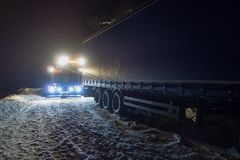 Ciężarowy wypadek uliczny przy nocą, na śnieżnej zimy drodze Silnie iluminująca Wrecker ciężarówka ciągnie ciężarówkę z śnieżnego Obraz Royalty Free
