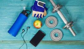 Ciężaru talerze, rękawiczki i smartphone na drewnianym tle, Zdjęcie Stock