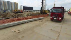 Ciężka czerwieni ciężarówka przychodzi miejsce budowa wielo- kondygnacja budynek z inną maszynerią na tle zbiory wideo