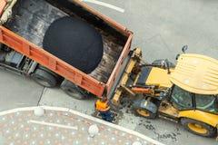 Ciężka przemysłowa usyp ciężarówka rozładowywa gorącego asfalt Miasta budowa drogi i odnowienia miejsce zdjęcie royalty free