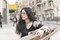 Ciężki metal kobiety stylowy obsiadanie na drewnianej ławce Zdjęcie Royalty Free