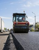 Ciężki wibracja rolownik przy asfaltowym brukiem pracuje na nowym budowy drogi miejscu naprawianie zdjęcie royalty free