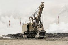 Ciężkiego wiadra górniczy ekskawator na śpioszka śladzie przeciw tłu zwarty fabryczny silny smog z dymienie kominami Fotografia Royalty Free
