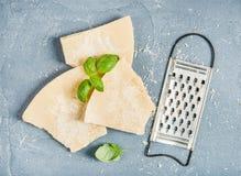 Cięcia Parmezański ser z metalu grater i świeżym basilem nad betonem textured tło Obraz Stock