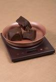 Cięcie i łamający kawałki ciemna czekolada na kuchenny elektronicznym ważymy Obraz Royalty Free