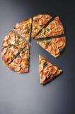 Cięcie plasterek pizza z pieczarkami, oliwkami i kiełbasami na czarnym tle, Fotografia Stock