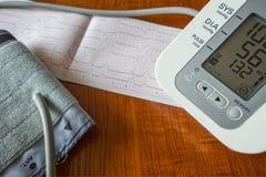 Ciśnienie krwi monitor, ciśnienie krwi monitoru mankiecik, kardiograma wydruk fotografia royalty free