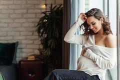 Ci??arna europejska kobieta w bia?ej bluzce i czarnych spodniach siedzi na windosill, eleganckiej i szcz??liwej kobiecie w ci??y, zdjęcia stock