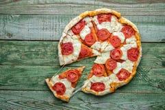 Cięcie w plasterek pizzy na zielonym stole Odgórny widok Zdjęcie Stock