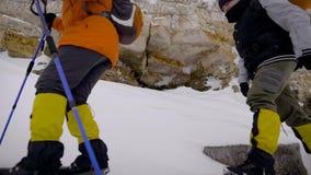 Ci-dessous tiré de deux randonneurs avec des sacs à dos et des poteaux de ski faisant un pas soigneusement sur des roches pour le banque de vidéos