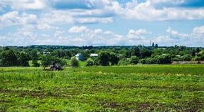 Ciągnik orze pole w tle wioska Fotografia Royalty Free