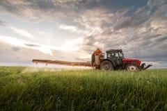 Ci?gnikowi opryskiwanie pestycydy przy pszenicznym polem zdjęcia stock